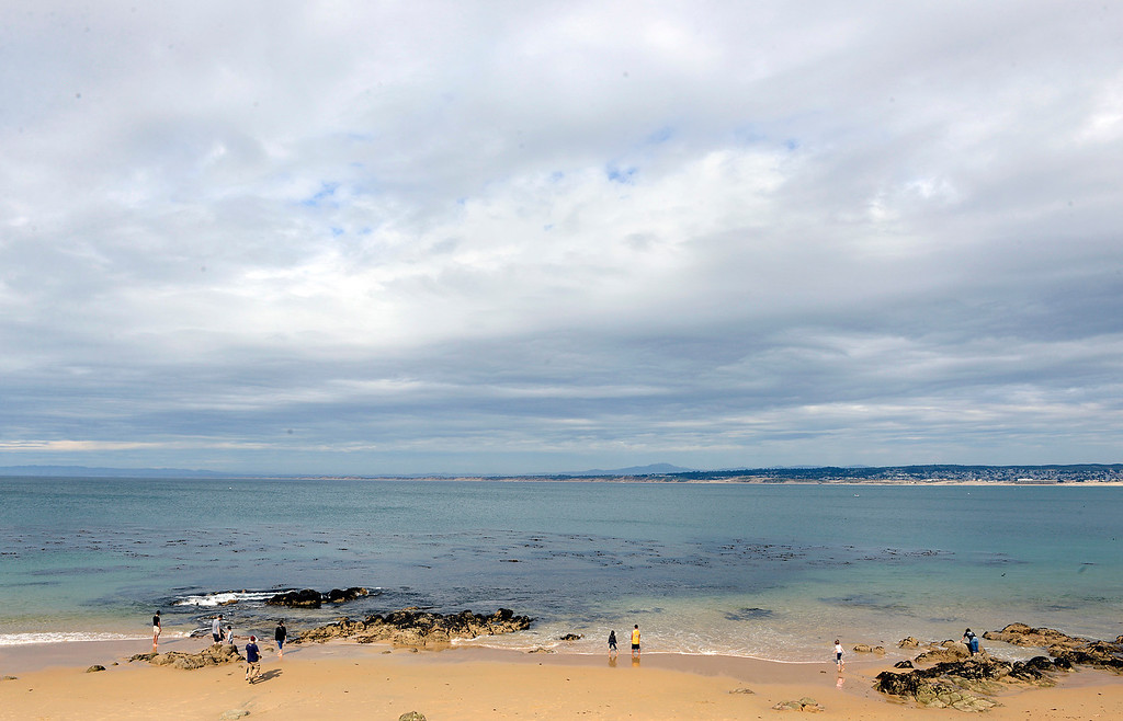 . Beach goers enjoy the sun at San Carlos Beach in Monterey as dark clouds move in to the north and east across the bay on Tuesday April 11, 2017. (David Royal - Monterey Herald)