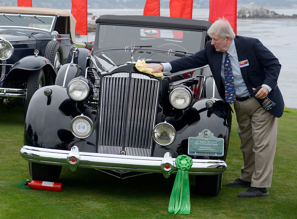 . Dave Kane cleans his 1937 Packard 1508 Twelve Rollston Convertible Victoria at the Pebble Beach Concours d\'Elegance on Sunday, August 26, 2018.  (Vern Fisher - Monterey Herald)