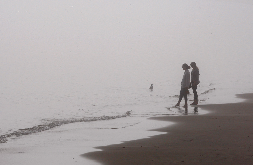 . Beach goers deal with the foggy conditions at Del Monte State Beach in Monterey on Monday, August 6, 2018.  (Vern Fisher - Monterey Herald)