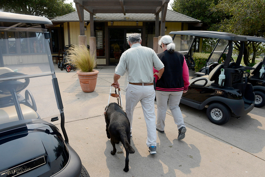 . Barbara Franco helps her husband U.S. Navy veteran, Carlos Franco with his service dog Miguel to the clubhouse at Bayonet and Black Horse Golf Club in Seaside on Tuesday, August 7, 2018.  Franco who is blind is learning golf through the PGA HOPE (Helping Our Patriots Everywhere) program at the Seaside golf course.  (Vern Fisher - Monterey Herald)