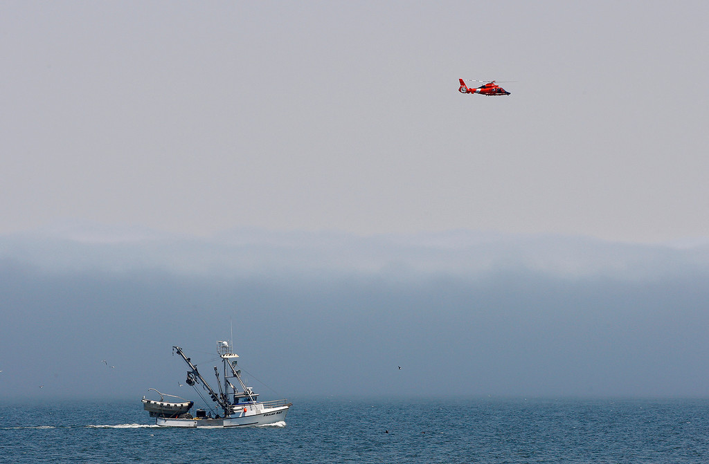 . A commercial fishing boat heads into Monterey Harbor as a Coast Guard helicopter flies overhead on Monday, August 6, 2018.  (Vern Fisher - Monterey Herald)