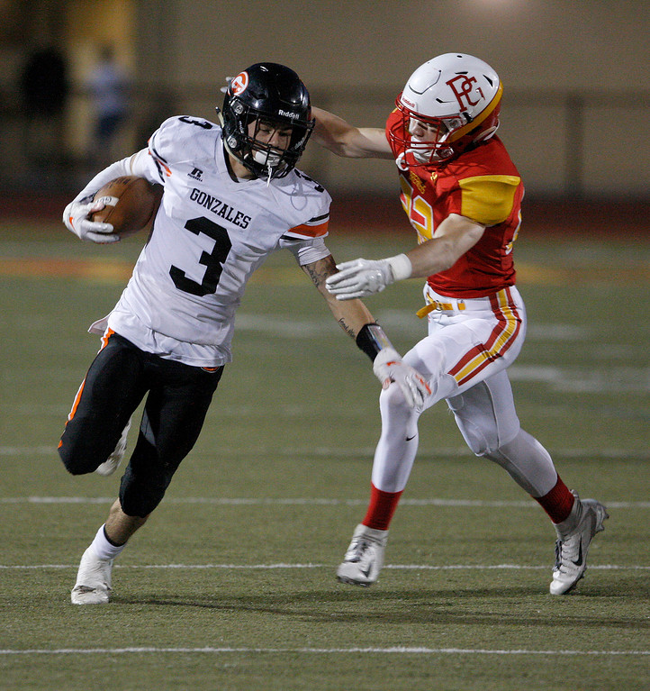 . Gonzales High School\'s Gilbert Payton Flores (3) runs past Pacific Grove High School defender Parker McAnally (22) for yards during their game in Pacific Grove on Friday, August 31, 2018.  (Vern Fisher - Monterey Herald)