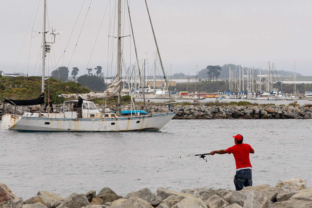 . A sailboat enters Moss Landing Harbor as a man fishes from the south jetty on Tuesday, September 4, 2018.  (Vern Fisher - Monterey Herald)