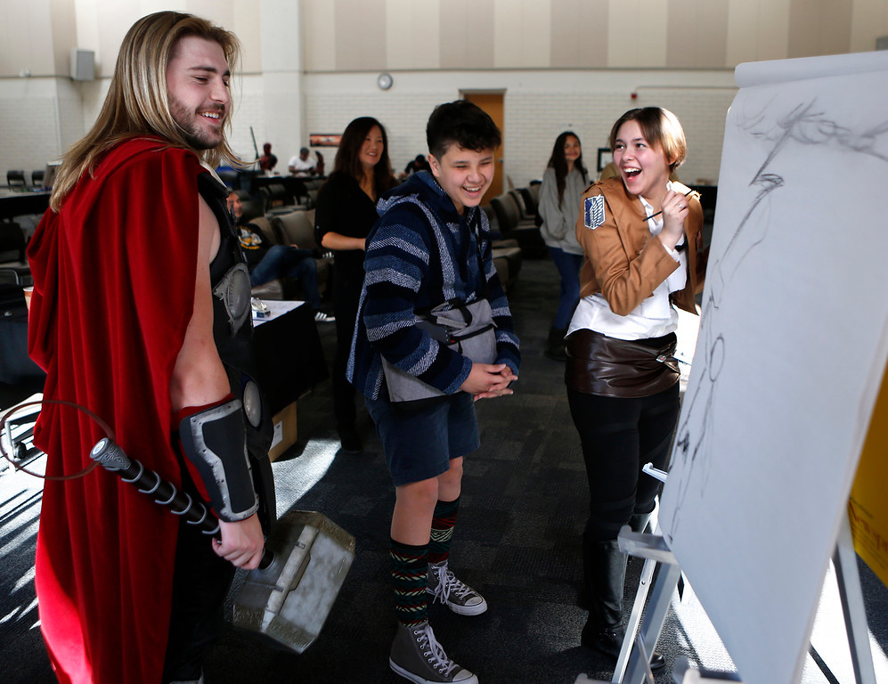 . Sammy Parachini, center, and Kaitlyn Ferguson laugh as Kevin Jasper who was dressed as Thor gives them feedback on their rendering of him during a timed drawing workshop at Salinas Valley Comic Con at Hartnell College in Salinas on Monday December 17, 2017. (David Royal/Herald Correspondent)