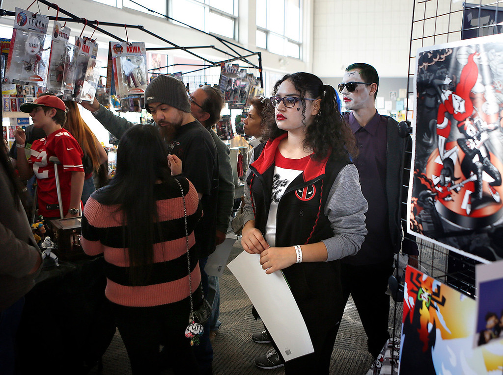. Leticia Ramirez, center, and her friend Cesar Ramirez are dressed as Suicide Squad characters Harlequin and the Joker as they brouse booths at Salinas Valley Comic Con at Hartnell College in Salinas on Monday December 17, 2017. (David Royal/Herald Correspondent)