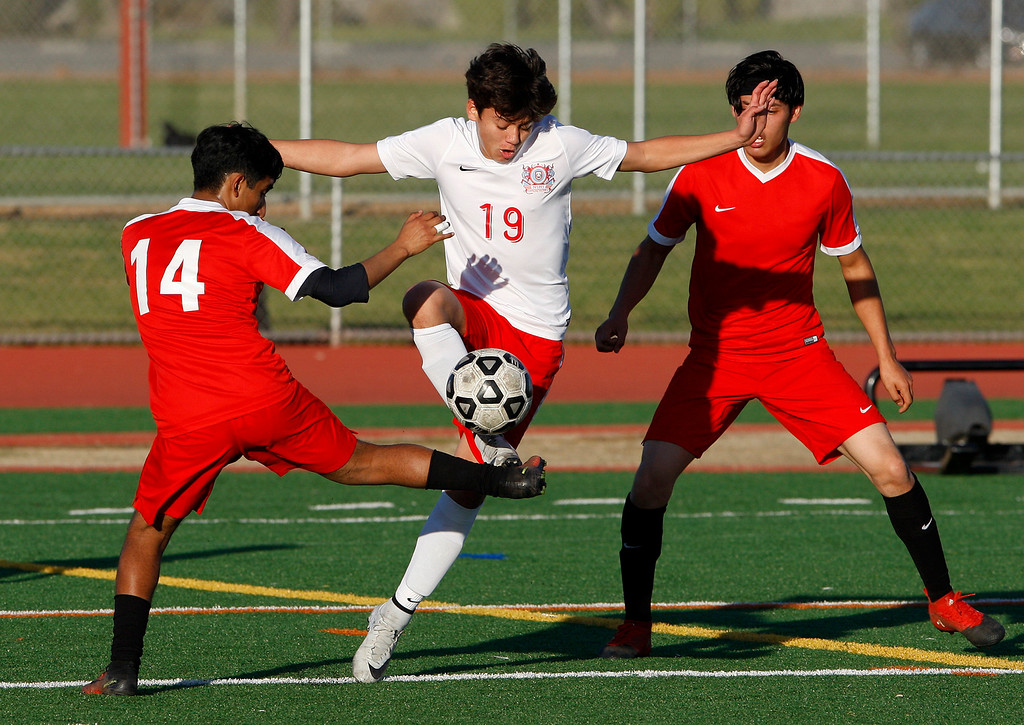 . North Salinas High\'s Esequiel Hernandez (19) battles Seaside High\'s Robert Sierra (14) during their match against North Salinas High in Salinas on Thursday, Jan. 4, 2018.  (Vern Fisher - Monterey Herald)