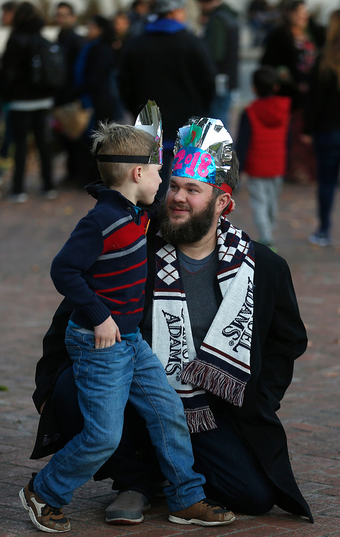 . Stephen Eberly holds his son Andrew, 7, after doning party hats they built during the First Night New Year Eve celebrations at Colton Hall in Monterey on Sunday December 31, 2017. (David Royal/Herald Correspondent)