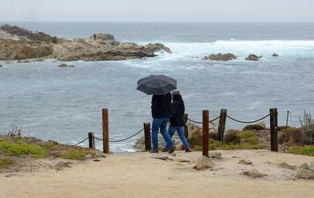 . A couple walks in the rain near Asilomar State Beach in Pacific Grove on Wednesday, Jan. 3, 2018.  (Vern Fisher - Monterey Herald)