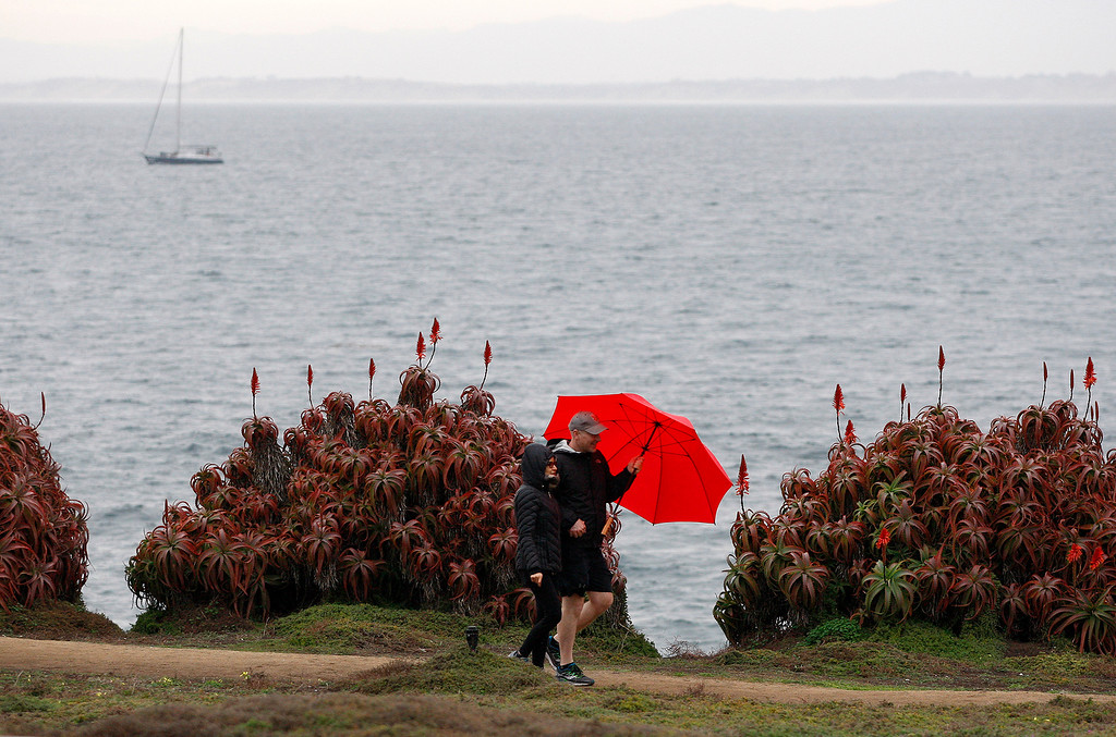 . A couple walks in the rain on Ocean View Blvd. in Pacific Grove on Wednesday, Jan. 3, 2018.  (Vern Fisher - Monterey Herald)