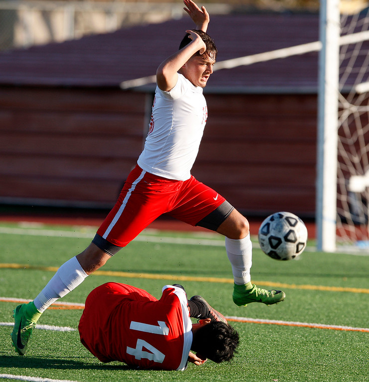 . North Salinas High\'s Oscar Regalado (16) jumps over Seaside High\'s Robert Sierra (14) during their match against North Salinas High in Salinas on Thursday, Jan. 4, 2018.  (Vern Fisher - Monterey Herald)