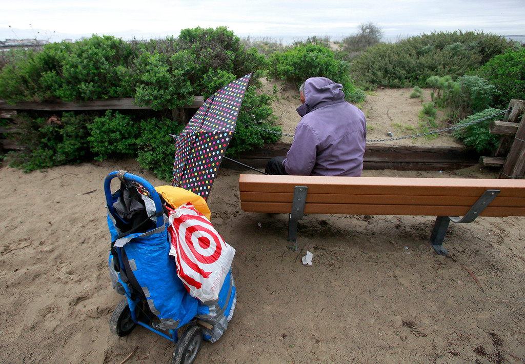 . A homeless man shelters himself from the rain and wind in Monterey on Wednesday, Jan. 4, 2017.  (Vern Fisher - Monterey Herald)