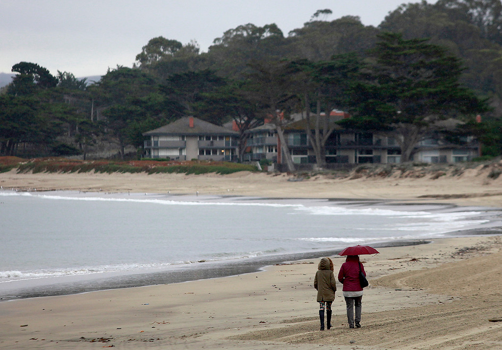 . People walk in the rain on Del Monte State Beach in Monterey on Tuesday, Jan. 3, 2017.  (Vern Fisher - Monterey Herald)