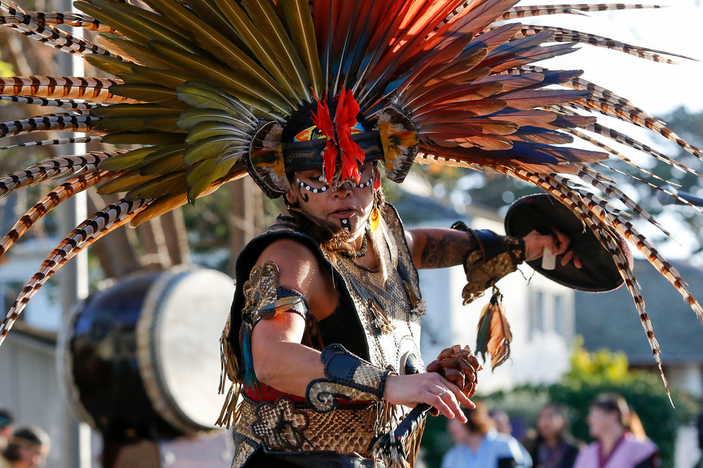 . A member of Calpulli Yaocuauhtli performs a traditional Aztec dance on Pacific St. in front of Colton Hall during the opening ceremony of First Night Monterey 2017 on Saturday, December 31, 2016 in Monterey, Calif. (Vernon McKnight/Herald Correspondent)