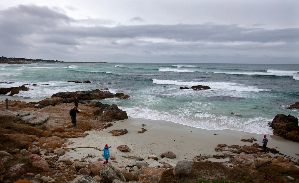 . People deal with rain and wind at Asilomar State Beach in Pacific Grove on Tuesday, Jan. 3, 2017.  (Vern Fisher - Monterey Herald)