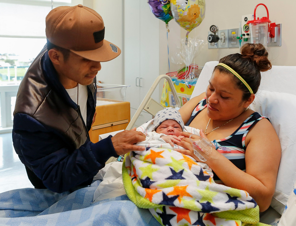 . Mariano Ruiz, left, leans in for a peek at his newborn son, Jonathan, being held by his mother, Maria Perez Gutierrez at Natividad Medical Center on Sunday, January 1, 2017 in Salinas, Calif. Jonathan was born at 2:26 a.m. and is the county\'s first newborn of the year. (Vernon McKnight/Herald Correspondent)