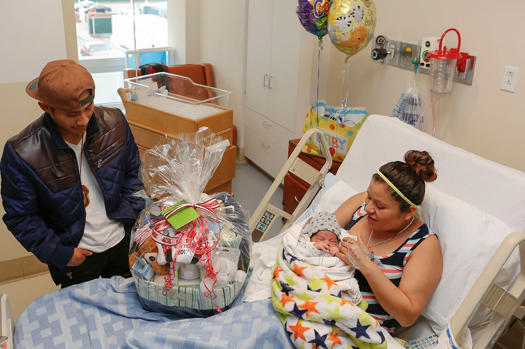 . Mariano Ruiz, left, looks at a gift basket given by the medical center to newborn son, Jonathan, being held by his mother, Maria Perez Gutierrez, for being the county\'s first newborn boy at Natividad Medical Center on Sunday, January 1, 2017 in Salinas, Calif. Jonathan was born at 2:26 a.m. and is the county\'s first newborn of the year. (Vernon McKnight/Herald Correspondent)
