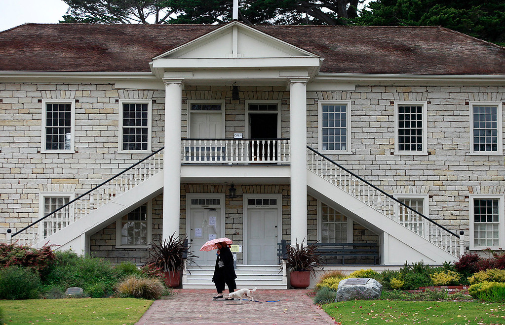 . A woman uses an umbrella while taking her dog for a walk at Colton Hall in Monterey on Tuesday, Jan. 3, 2017.  (Vern Fisher - Monterey Herald)