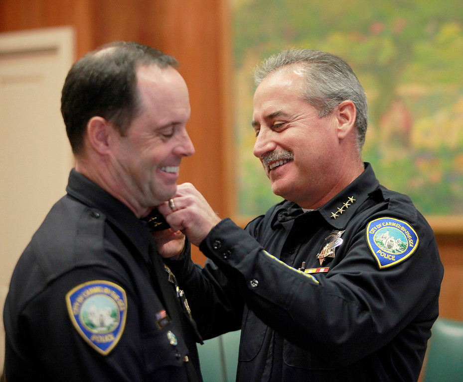 . Carmel\'s new police chief Paul Tomasi receives bars from outgoing chief Mike Calhoun in a ceremony in the city council chambers on Friday, Dec. 30, 2016.   (Vern Fisher - Monterey Herald)