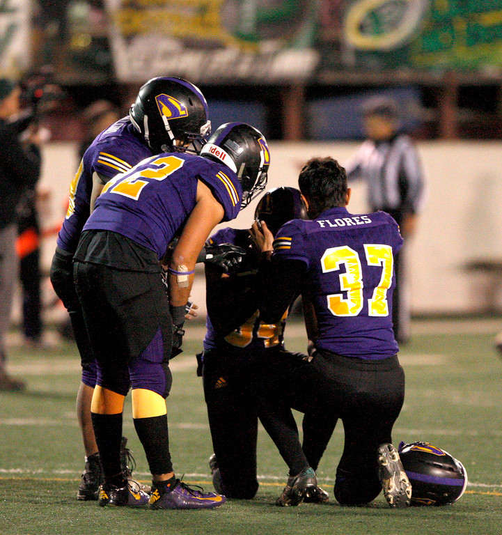 . Salinas High kicker Adrian Hernandez (34) is consoled by teammate Alan Flores (37) after missing an extra point in overtime to Placer in their Division 4-AA CIF State Football Championship Bowl Game on Friday, Dec. 8, 2017 in Salinas.  Placer High beat Salinas High in overtime 43-42 to advance to the CIF State Final.  (Vern Fisher - Monterey Herald)