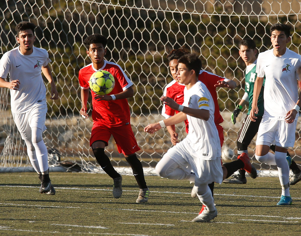 . Seaside\'s Alexandro Gudino, center left, and Monterey\'s Ariel Perez battle for a loose ball in front of Monterey\'s goal during boys soccer at Monterey High School on Wednesday December 13, 2017. (David Royal/Herald Correspondent)