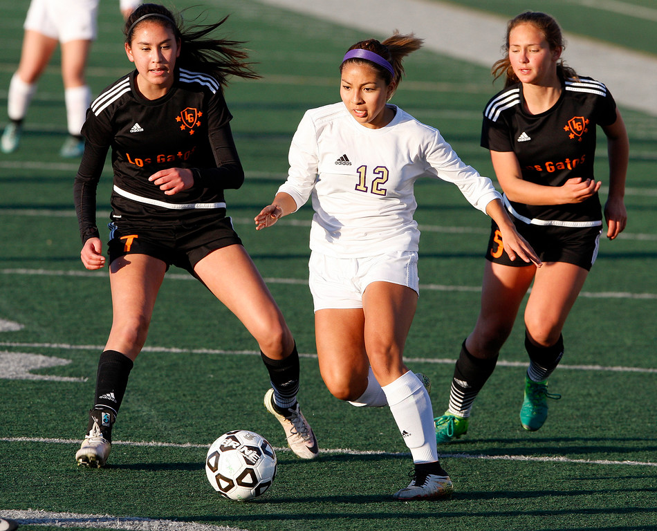 . Salinas High\'s Tammy Torres (12) eludes Los Gatos High defenders Isabella Scott (7) and Loie Bonnett (5) during their CCS DIV soccer playoff match against in Salinas on Wednesday, Feb. 21, 2018.   (Vern Fisher - Monterey Herald)