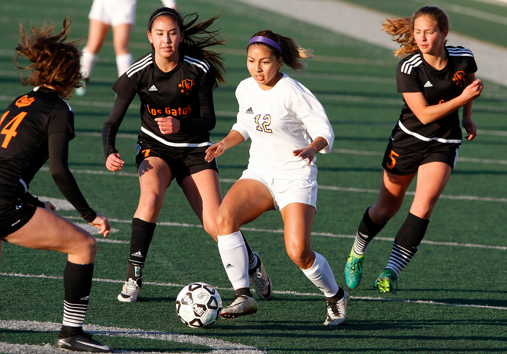 . Salinas High\'s Tammy Torres (12) eludes Los Gatos High defenders Caroline Damore (14), Isabella Scott (7) and Loie Bonnett (5) during their CCS DIV soccer playoff match against in Salinas on Wednesday, Feb. 21, 2018.   (Vern Fisher - Monterey Herald)