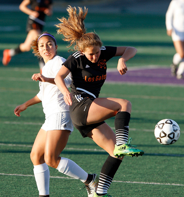 . Salinas High\'s Tammy Torres (12) battles Los Gatos High defender Loie Bonnett (5) during their CCS DIV soccer playoff match against in Salinas on Wednesday, Feb. 21, 2018.   (Vern Fisher - Monterey Herald)