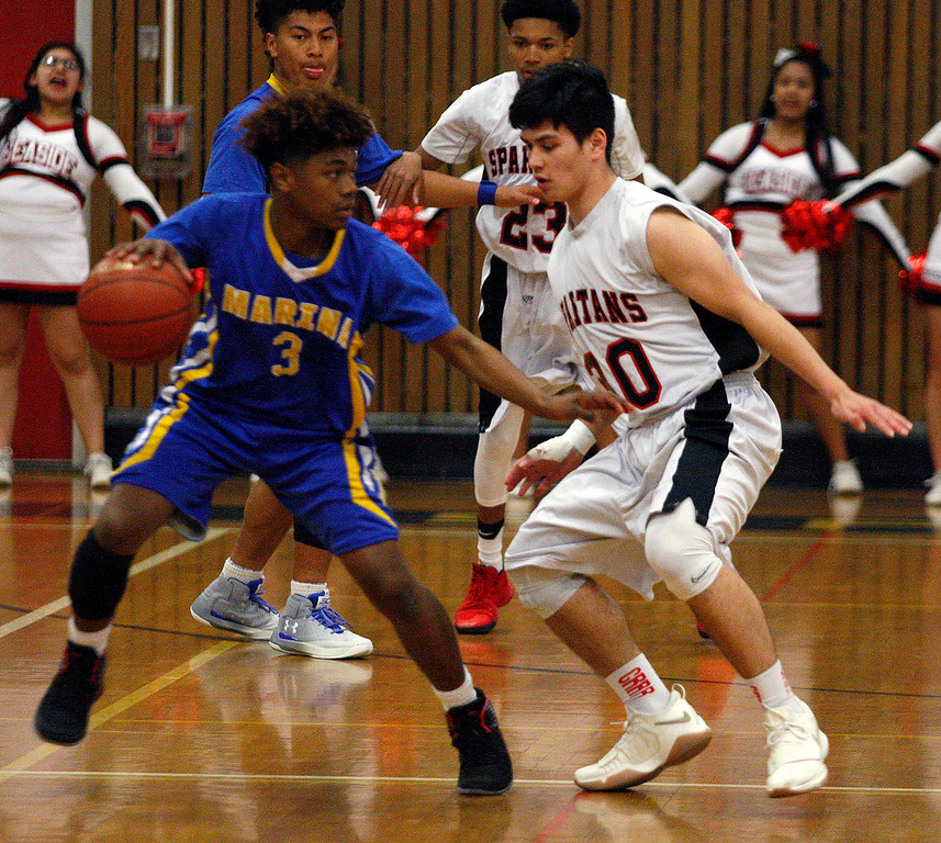 . Marina High\'s Cottrell Ealey (3) battles Seaside High\'s Jordan Banon (30) during their CCS DIV boys basketball playoff game at Seaside High on Tuesday, Feb. 20, 2018.  (Vern Fisher - Monterey Herald)