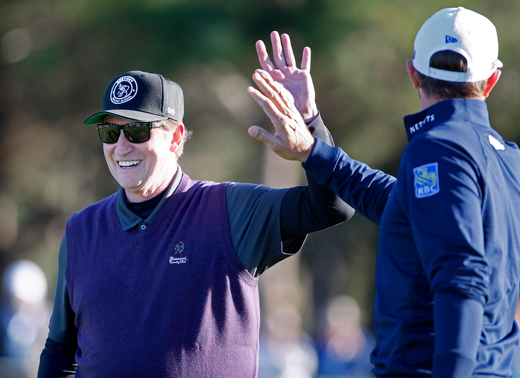 . Wayne Gretzky gets a high five from player partner Dustin Johnson at Spyglass Hill Golf Course during the first round of the AT&T Pebble Beach Pro-Am on Thursday, Feb. 8, 2018.  (Vern Fisher - Monterey Herald)