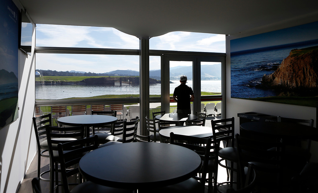 . Josh Lippold looks out the window of a luxury box above the 17th green at Pebble Beach Golf Links after checking velcro fabric work his company installed during preparations for the AT&T Pebble Beach Pro-Am on Sunday February 4, 2018. Photo by David Royal)