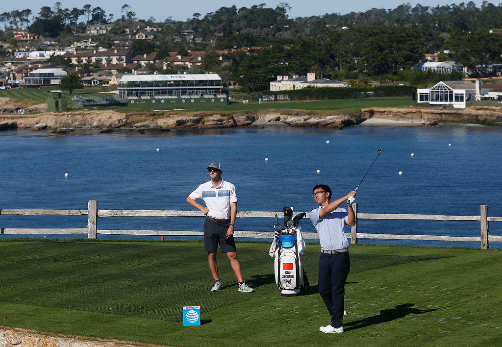 . Pro golfer Zecheng Dou, 21, tees off from the seventh hole under sunny conditions during practice rounds before the AT&T Pebble Beach Pro-Am Pebble Beach Golf Links on Monday February 5, 2018. Photo by David Royal)