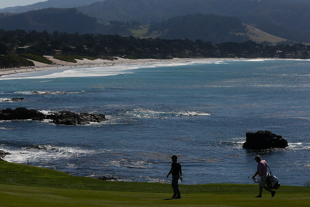 . Pro golfer David Summerhays and his caddy walk along the eighth fairway as sunshine soaks Carmel Bay behind him during practice rounds before the AT&T Pebble Beach Pro-Am Pebble Beach Golf Links on Monday February 5, 2018. Photo by David Royal)