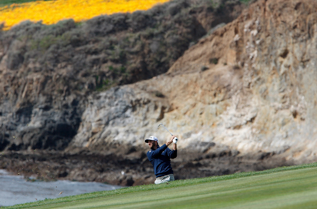 . Dustin Johnson hits his second shot on the 9th hole at the Pebble Beach Golf Links during the final round of the AT&T Pebble Beach Pro-Am on Sunday, Feb. 11, 2018.   (Vern Fisher - Monterey Herald)