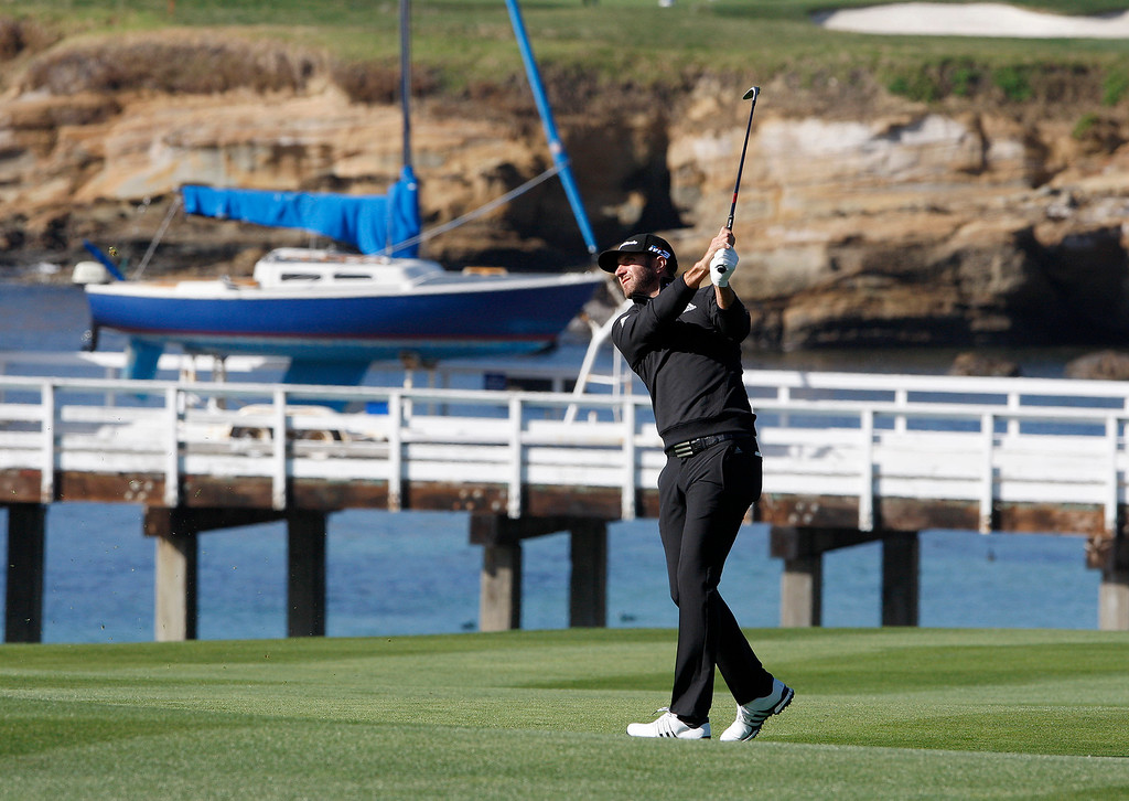 . Dustin Johnson watches his approach shot on the fourth hole at the Pebble Beach Golf Links during the third round of the AT&T Pebble Beach Pro-Am on Saturday, Feb. 10, 2018.  (Vern Fisher - Monterey Herald)
