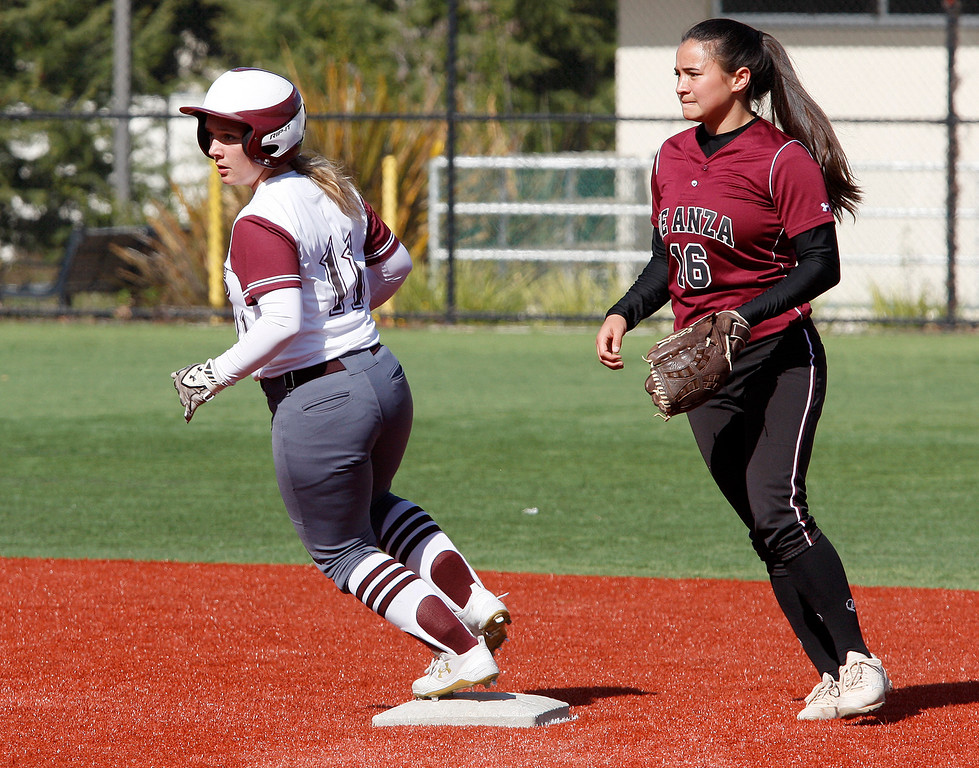 . Monterey Peninsula College\'s Catalina MacDonald (11) rounds second base as De Anza College\'s Danielle Pati (16) covers the base during their game against De Anza College on Tuesday, Feb. 13, 2018.  (Vern Fisher - Monterey Herald)