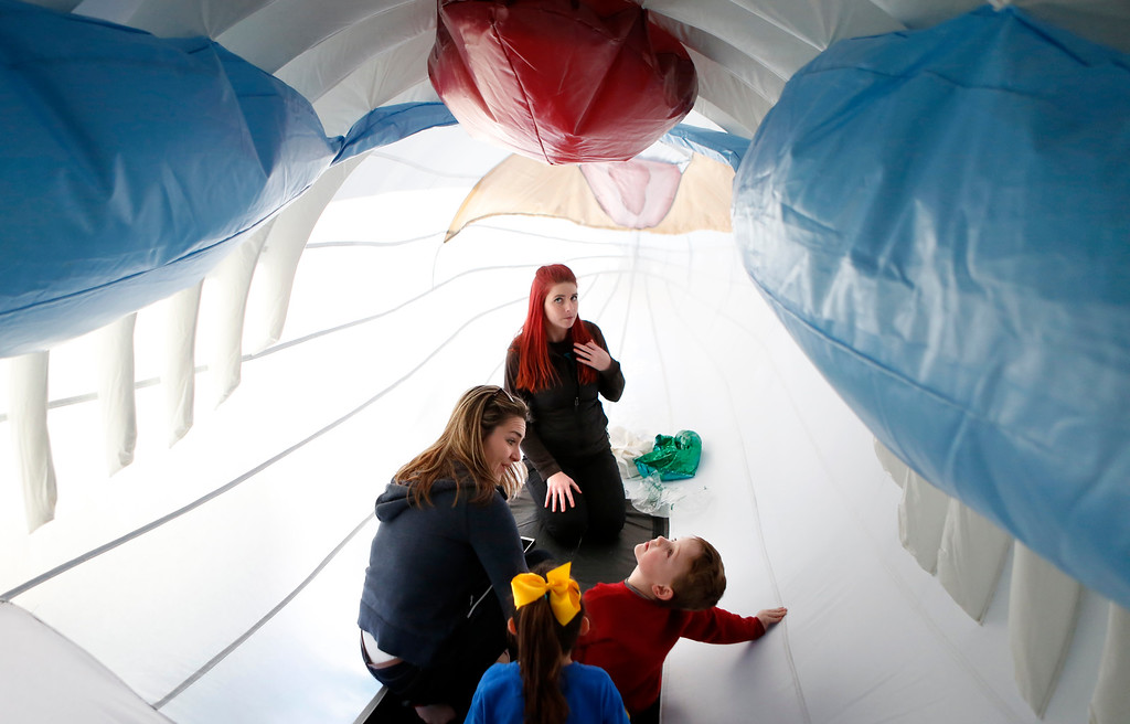 . Katie Bennett, center rear, of Save the Whales describes the organs inside a giant inflatable humpback whale to Ashley Hansen, her son Alexander, 4, and Madison Sprouls, 5, at a both hosted by Save the Whales and Monterey High Schools MAOS program during Whalefest Monterey at the base of Fisherman\'s Wharf in Monterey on Saturday January 27, 2018. (David Royal/Herald Correspondent)