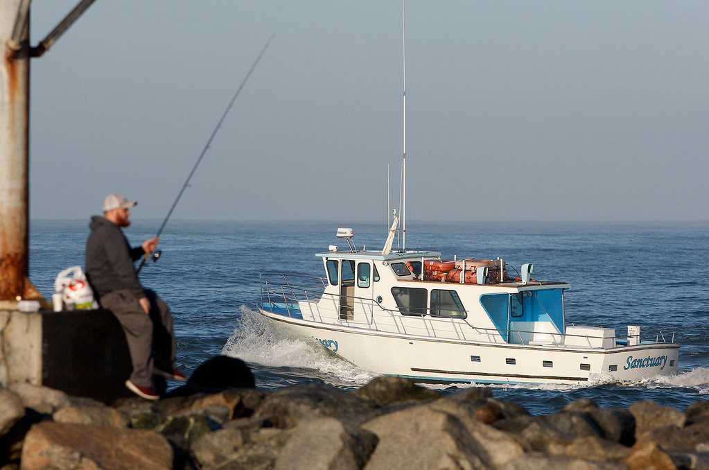 . A man fishes off the south jetty as a commercial vessel heads out of the Moss Landing Harbor on Friday, Jan. 26, 2018.  (Vern Fisher - Monterey Herald)