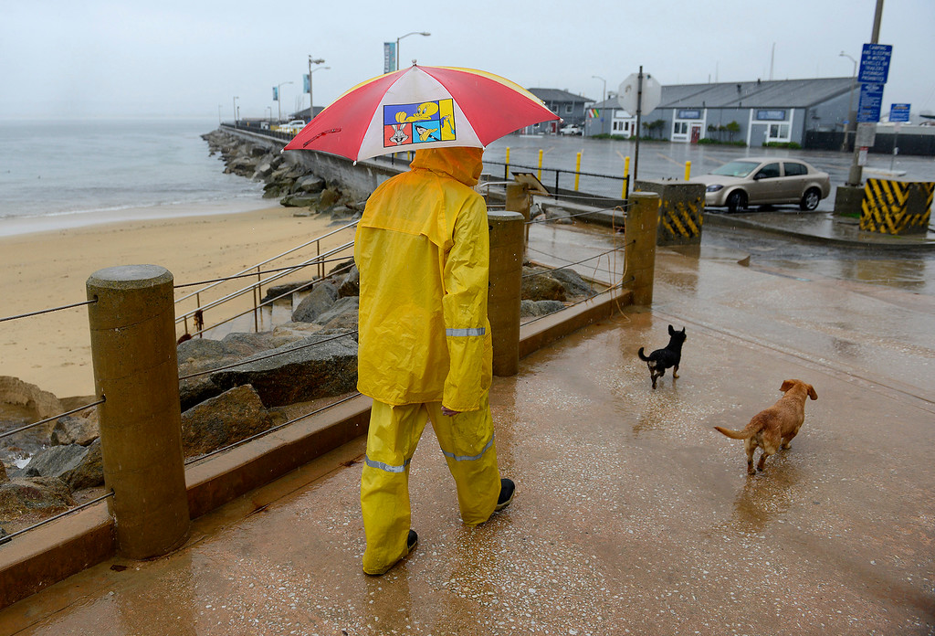 . A man takes his two dogs for a walk in the rain at San Carlos Beach Park in Monterey on Monday, Jan. 8, 2018.  (Vern Fisher - Monterey Herald)