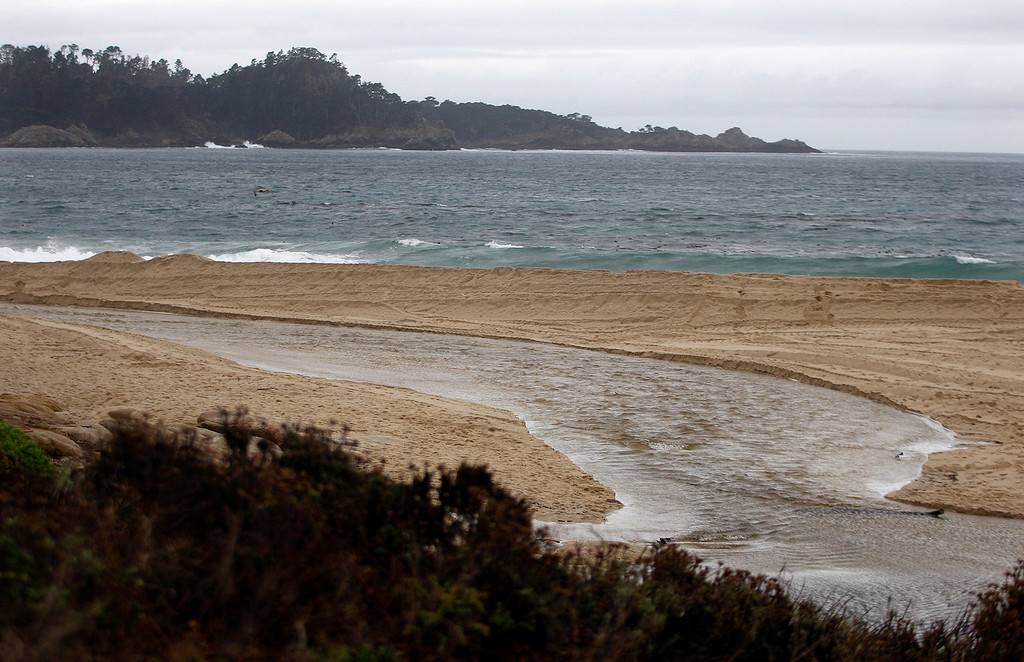 . The Carmel River flows to the sea on Tuesday, Jan. 9, 2018.  The Monterey County Resource Management Agency brought in special crews to work at the Carmel Lagoon area to lower and contour the sandbar at Carmel River State Beach as part of its lagoon management plan.  (Vern Fisher - Monterey Herald)