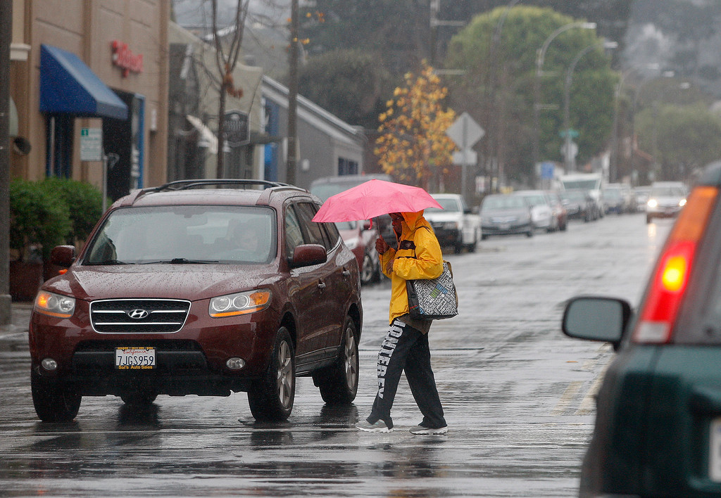. Pedestrians and commuters in Monterey had to deal with heavy rain on Monday, Jan. 8, 2018.  (Vern Fisher - Monterey Herald)