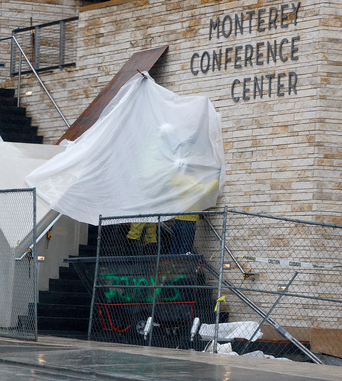 . Workers use a plastic tarp to stay dry while working on the outside of the new Monterey Conference Center during a heavy rain shower on Monday, Jan. 8, 2018.  (Vern Fisher - Monterey Herald)