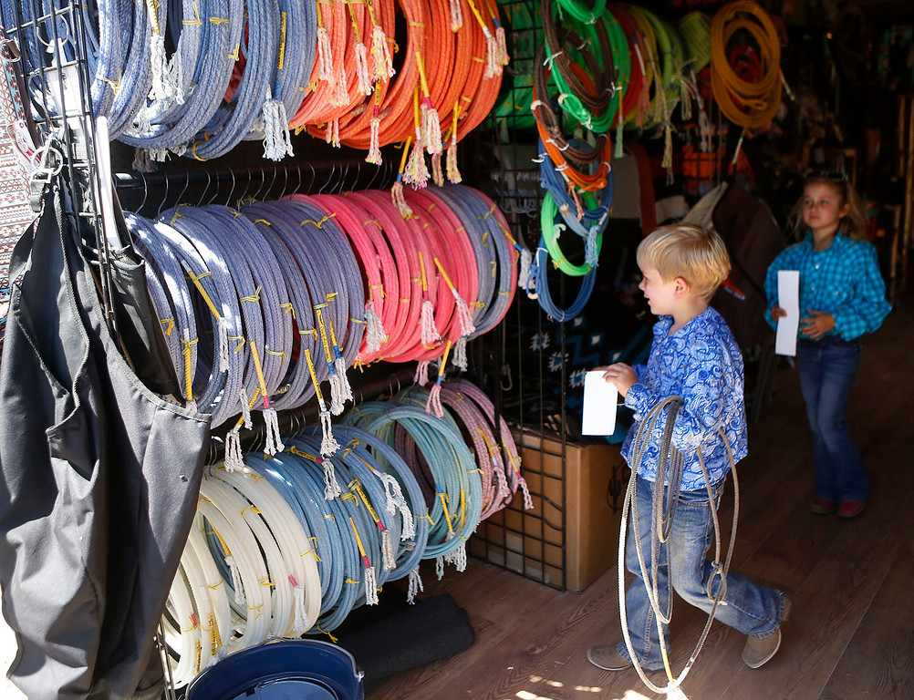 . Max Cohn, 6, and his sister Maci, 8, look at roping gear inside the Steer Gear trailer during the California Rodeo Salinas at the rodeo grounds in Salinas on Thursday July 20, 2017. The children\'s father is Ed Cohn a pro roper.  (David Royal/Herald Correspondent)