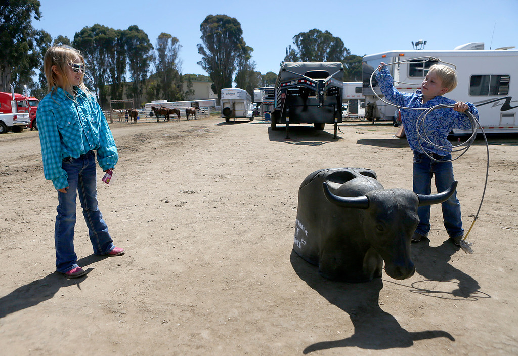 . Maci Cohn, 8, and her brother Max, 6, take turns roping a roping dummy outside the Steer Gear trailer during the California Rodeo Salinas at the rodeo grounds in Salinas on Thursday July 20, 2017. Their father Ed Cohn is a pro roper. (David Royal/Herald Correspondent)