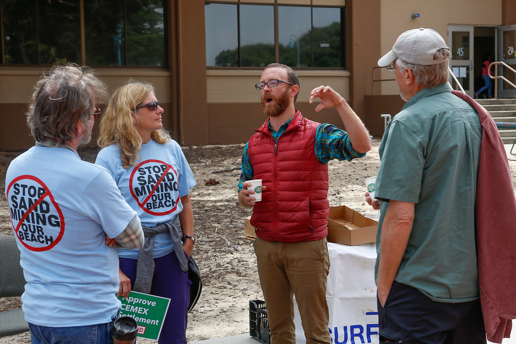 . Kevin Miller of Surfrider Foundation, center, talks with supports of the Coastal Commission\'s proposed settlement to remove the CEMAX sand mining plant in Marina during a rally outside the World Theater at CSU Monterey Bay on Thursday, July 13, 2017 in Seaside, Calif. (Vernon McKnight/Herald Correspondent)