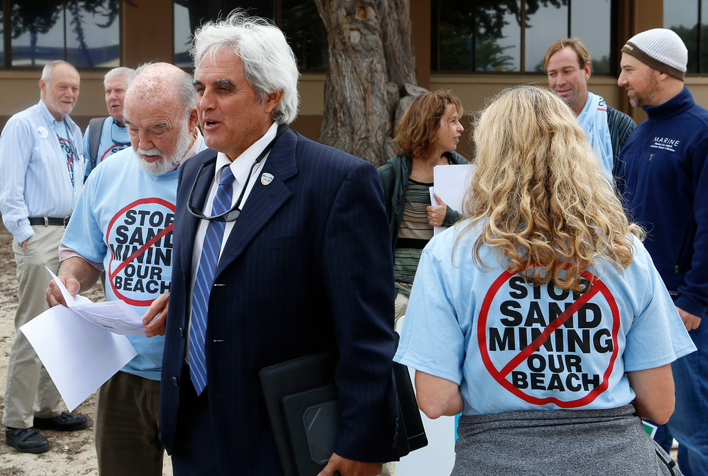. A number of supporters of the Coastal Commission\'s proposed settlement to remove the CEMAX sand mining plant in Marina including Marina mayor Bruce Delgado, center, rally outside the World Theater at CSU Monterey Bay on Thursday, July 13, 2017 in Seaside, Calif. (Vernon McKnight/Herald Correspondent)