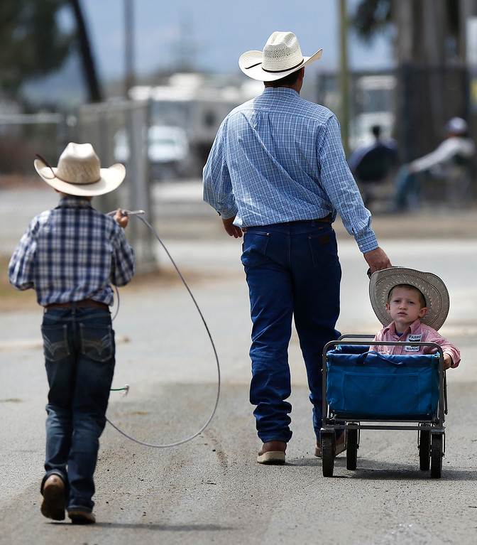 . Eric Lake and sons Ward, 4, and Gus, 9, head to their trailer behind the California Rodeo Salinas at the rodeo grounds in Salinas on Thursday July 20, 2017. (David Royal/Herald Correspondent)