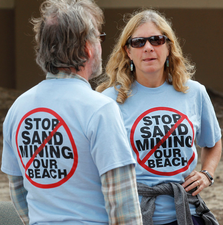 . Marco Poehner of Monterey, left, and Cammy Torgenrud of Carmel, both supporters of the Coastal Commission\'s proposed settlement to remove the CEMAX sand mining plant in Marina converse during a rally outside the World Theater at CSU Monterey Bay on Thursday, July 13, 2017 in Seaside, Calif. (Vernon McKnight/Herald Correspondent)