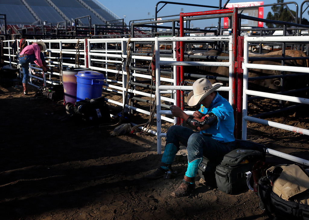 . Mike Lee attaches an arm brace prior to competing in the Professional Bull Riding event at the Salinas Rodeo grounds on Wednesday July 19, 2017. (David Royal/Herald Correspondent)