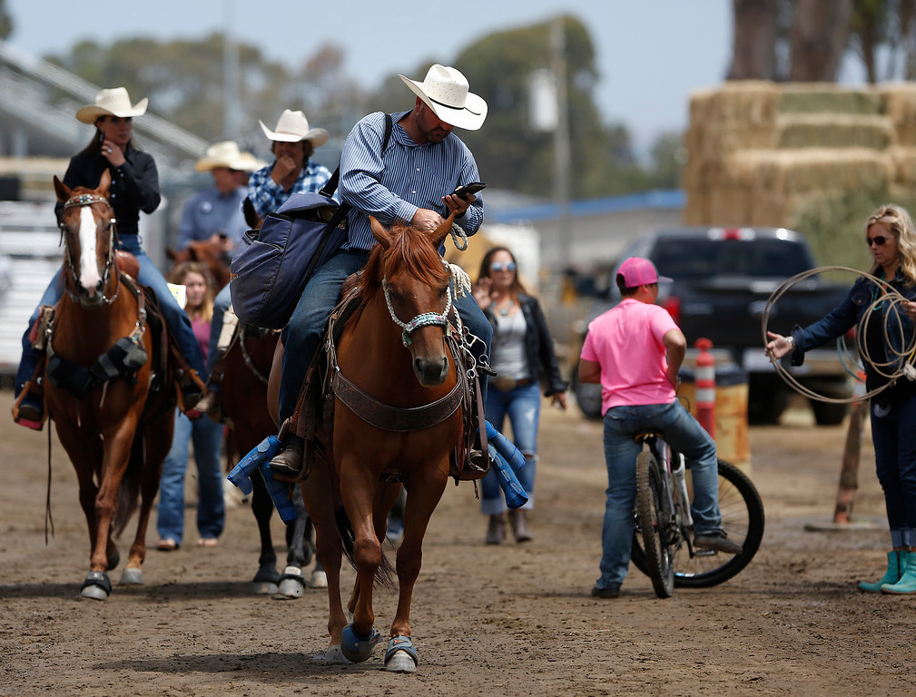 . A cowboy checks his cell phone between events during the California Rodeo Salinas at the rodeo grounds in Salinas on Thursday July 20, 2017. (David Royal/Herald Correspondent)