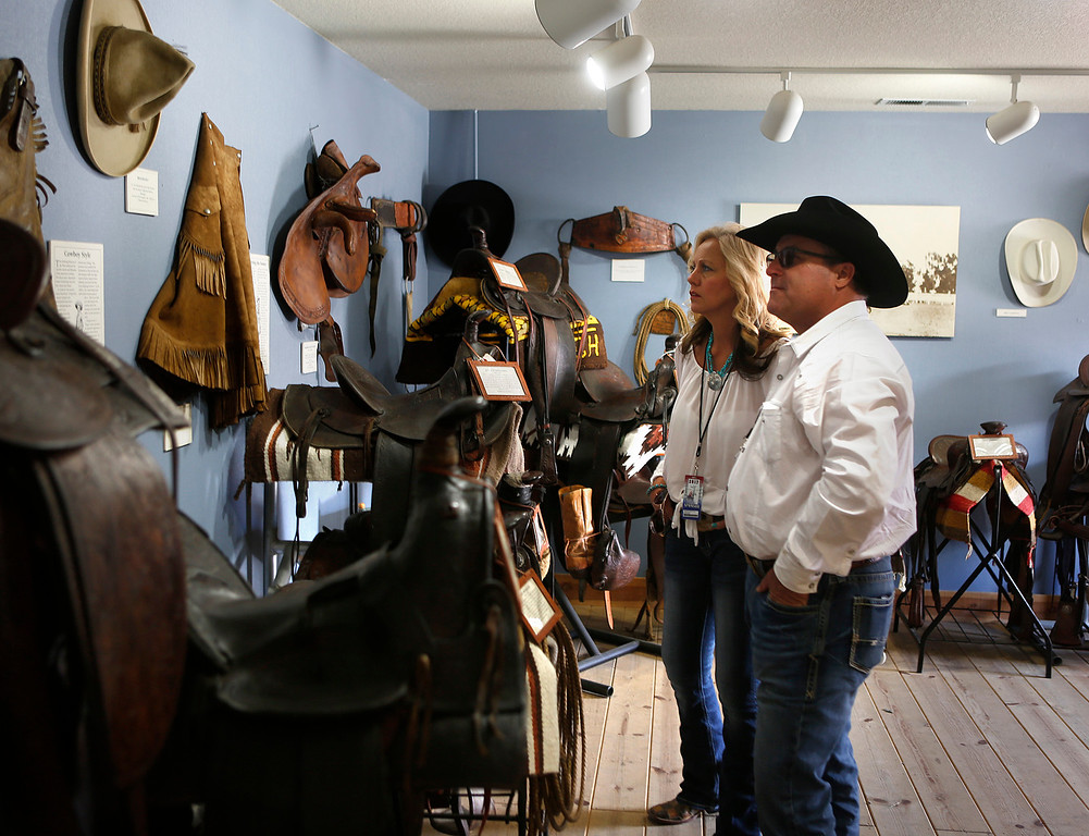 . Tina McCash and her boyfriend Brad Zittlow look over a display of historical saddles and other cowboy gear inside The California Rodeo Heritage Museum at the rodeo grounds in Salinas on Saturday July 22, 2017. (David Royal/Herald Correspondent)